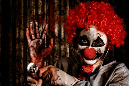 payaso: retrato de Halloween de un médico payaso aterrador holding amputó la mano en la descomposición severa con fonendoscopio médica. Pulso de los gusanos