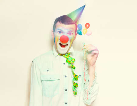 clowning: Laughing Retro Clown Holding Celebration Balloons And Streamers While Celebrating A Happy Birthday