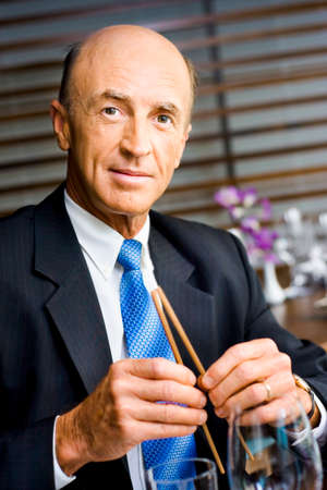 chief executive officers: Senior Business Man Breaks Chopsticks While On A Executive Meeting At A Restaurant In China, In A Depiction Of Breaking Into The Chinese Business Marketplace