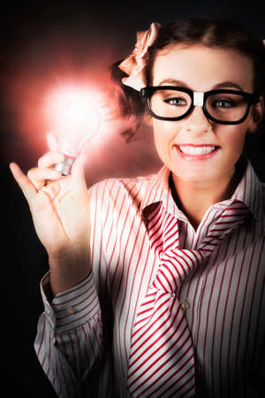 dweeb: Intelligent Nerd Girl Holding A Illuminated Light Bulb In A Brainy Depiction Of A New Business Innovation