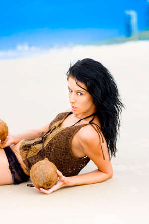 quietude: Beautiful Young Woman With Black Hair And Fierce And Enticing Expression Posing On A White Sand Beach