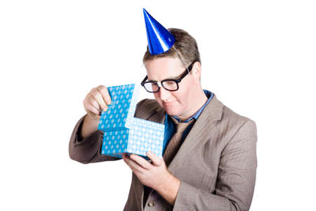 farewell party: Isolated businessman in brow suit and party hat opening dotted box. Business bonus