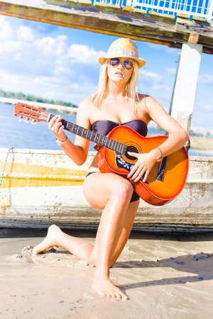 serenade: Beautiful Young Blond Girl Performing A Musical Sea Shore Serenade Song On A Wooden Guitar In Summertime Fashion