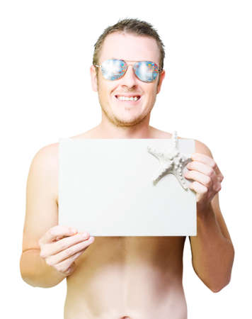 beach hunk: Happy smiling person advertising beach holiday discounts and sale specials while holding a blank copyspace board with star fish on white background