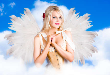 clasping: Gorgeous Blond Woman Flying Above A Heavenly Cloud With Soft Fairy Wings While Clasping Heart In A Depiction Of Cupid The Angel Of Love