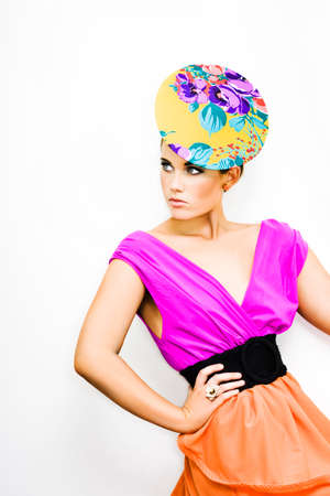 neckline: Beautiful fashionable girl wearing a colourful vintage pillbox hat and shocking pink plunging neckline blouse posing on white