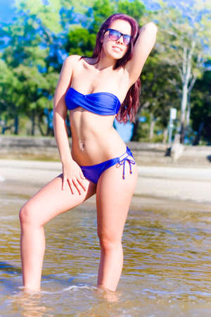 bather: Attractive Pretty Woman Wearing Blue Bikini And Fashion Sunglasses Strikes A Modeling Pose In The Shallow Sea Water While Sunbathing At The Beach