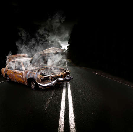 roadside assistance: Rusty Overheated And Broken Down Vehicle Wreck Steaming Up Clouds Of Smoke And Fumes On The Side Of A Atmospheric Road In A Roadside Assistance Conceptual Stock Photo