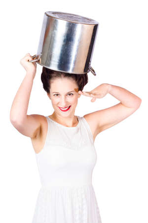 duties: Fun cooking picture of an attractive young pin up lady saluting with cook pot on head when reporting for kitchen duties. Food prep concept Stock Photo
