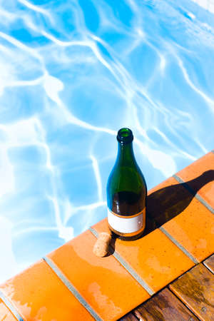rimmed: A green open champagne bottle with blank gold rimmed label standing alongside its cork on wet tiles surrounding a sparkling blue swimming pool in a holiday resort concept Stock Photo