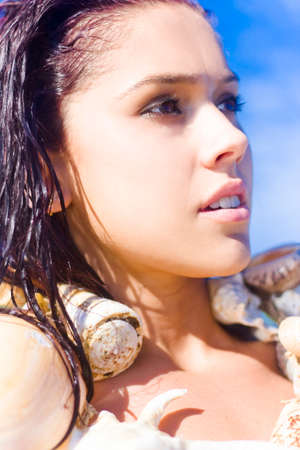 musing: Focus On The Face Of A Dreaming Thinking And Pensive Woman Looking Out Over The Ocean While Wearing Sea Shells In A Dream Holiday Concept