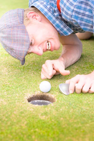 bending down: Sport Concept Of A Crazy Golfer Man Bending Down On A Golf Course Green While Screaming At His Ball Millimeters Away From The Hole