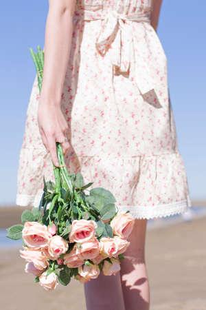 donna innamorata: Emotivo giovane donna in piedi su una costa Spiaggia di partecipazione su un fiore della Rosa del mazzo in attesa di un Romance reale Dal Suo Solo il vero amore