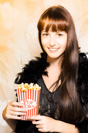 buttered: Happy smiling young woman in a feather boa holds an iconic traditional red and white striped box of delicious hot buttered popcorn during the intermission at showtime