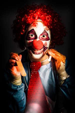 payaso: Payaso asustadizo del doctor médico a punto de realizar un examen oral sobre la víctima con la luz de la mano y depresor de lengua. La locura en la tortura médica