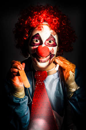 crazed: Scary medical clown doctor about to perform oral examination on victim with hand light and tongue depressor. Madness in medical torture