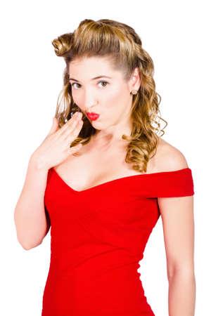 silencio: Aislado retrato de una chica pinup retro sorprendido con castaños cincuenta años rubios el peinado de la mano a los labios rojos en estado de shock silencio sobre fondo blanco Foto de archivo