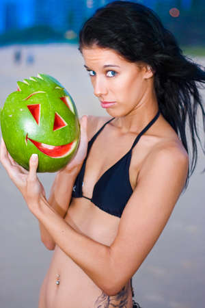 quizzical: Beautiful Blue Eyed Bikini Woman With Joking And Teasing Expression Holding A Carved Happy Face Watermelon As If She Finds The Situation To Be Humorous