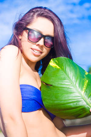 humid: Beautiful Young Woman Wearing Bikini And Sunglasses Fanning Herself In The Summer Sun With A Large Green Tree Leaf In A Hot Heat And Humid Climate Concept