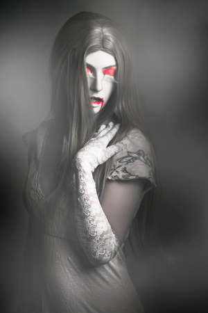 scary halloween: Dark fine art portrait of a beautiful vampire woman with long grey hair standing in a fog cover cemetery. Twilight nightmare