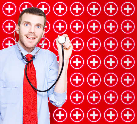 medical practitioner: Happy Smiling General Practitioner Doctor Holding Stethoscope On Red Medical Cross Background