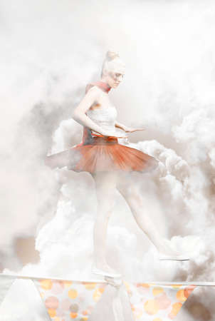 ballerina fairy: Danger Ballerina In Tutu Or Leotard Walking A Fine Line Of Rope Or Tightrope In The Cloudy Heaven Or Heavens In A Fairy Dreamy Wonderland Representing Risk Stock Photo