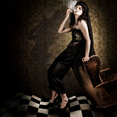 sexy brunette woman: Artistic Fashion Photo Of Beautiful Avant-garde Woman Smoking Cigar In A Dim Vintage Interior While Portraying The Twisted And Edgy Look Of Grunge Fashion Stock Photo