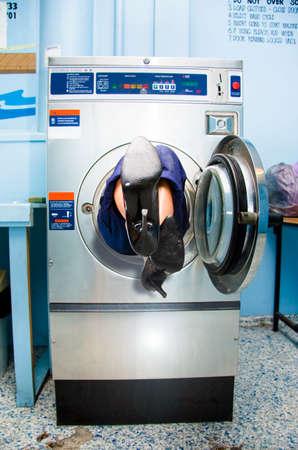 cargador frontal: Los pies de una se�ora de la limpieza del palillo fuera del extremo de una m�quina cargadora frontal lavadora Ella qued� atrapado En al intentar limpiar en una fotograf�a humor�stica trabajo de la casa Foto de archivo