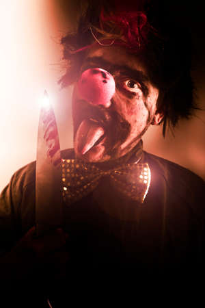 frightening: Sinister Portrait Of A Frightening Evil Clown With Creepy Expression Holding A Bloody Knife Or Cleaver Stock Photo