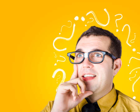 dweeb: Inquisitive dorky male troubleshooting problem when thinking with look of discovery. Question mark background Stock Photo