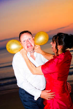 horseplay: Comical Wedding Moment Captured In Front Of A Beach Sunset As A Newly Wed Bride Pretends To Strangle And Choke Her Groom With Balloons