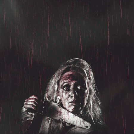 gothic girl: Dark vintage horror poster with masthead copyspace of a evil dead zombie girl holding blood stained hand saw in falling red rain. Night terrors Stock Photo