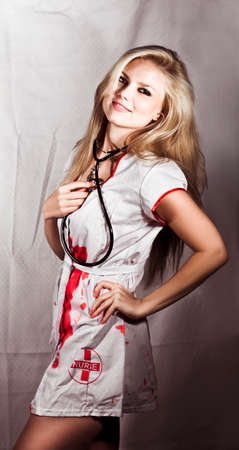 Evil Nurse Concept. Smiling pretty evil nurse wearing a stethoscope and bloodstained uniform Stock Photo