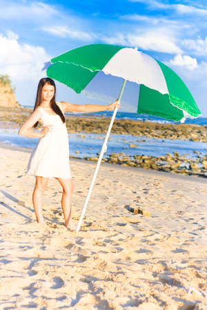 mini umbrella: Fit And Lovely Beach Babe Standing Under Parasol While On A Sandy Ocean Retreat In A Summer Holiday Concept