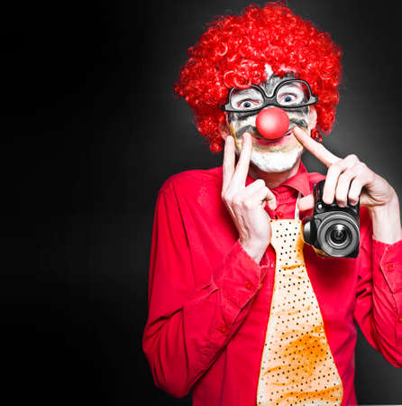 clowning: Comical Photograph Of A Smiling Clown Holding Digital Camera In A Cheesy Depiction Of A Happy Snap On Dark Studio Background Stock Photo