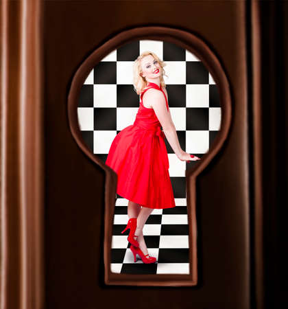 view through door: Retro fashion portrait of a stylish sensual pinup girl dancing in bright red dress. Image view through door keyhole Stock Photo