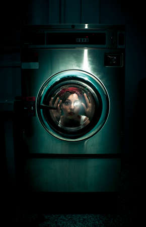 attractive girl: A Frightened Worried And Scared Domestic Housekeeper Woman Becomes Stuck Inside Her Washing Machine When Cleaning In A Crazy And Dark Cleaning Problems Concept Stock Photo