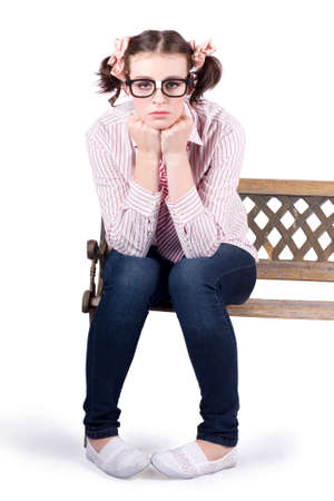 morose: Isolated portrat of a young depressed nerdy girl sitting alone on park bench