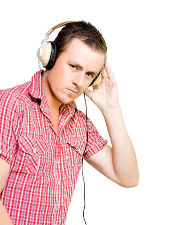 ear checked: Young man with a serious expression in a red checked shirt wearing a pair of large wired circumaural headphones isolated on white