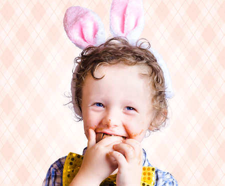 bunny ears: Child Eating Chocolate Easter Egg With Smile In A Easter Fun Concept On Copy Space