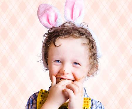 chocolatera: Niño que come el chocolate del huevo de Pascua con la sonrisa en una Pascua Concepto Diversión En Espacio en blanco