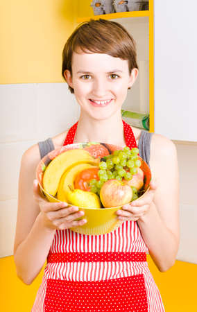 youthful: Smiling woman with short brunette hair holding fresh fruit bowl filled with an assortment of bananas apples and grapes, on interior background Stock Photo