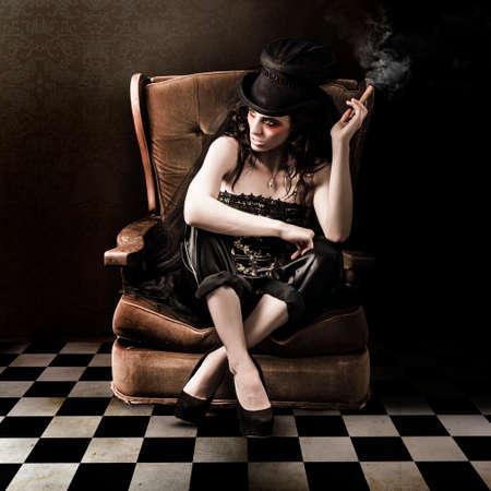 mujeres elegantes: Foto de la bella de una señora joven de la manera que se sienta en el sofá por la vendimia en el grunge interior