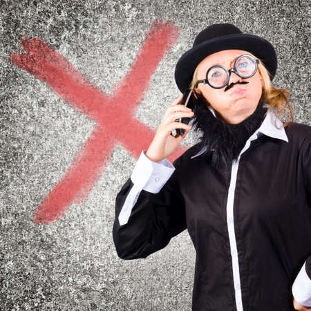 mobile communication: Cross businessman frowning while talking on mobile phone with x concrete wall background in a depiction of a communication breakdown