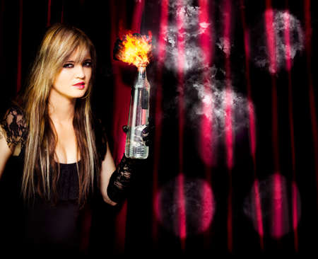 apprehended: A beautiful blonde hoodlum captured in the act of arson as she holds a burning petrol bomb in her gloved hand intent on setting the theatre on fire conceptual of being caught in the act