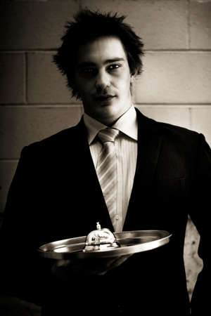 prestige: Duotone Portrait Of A Retail Salesman Or Waiter Holding Service Bell On A Silver Platter In A Representation Of Prestige Silver, Platinum Or Gold Service
