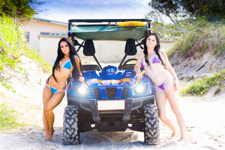 babes: Two Sexy Female Beach Babes Pose Beside A Surf Rescue Dune Buggy 4x4 Car On A Sandy Beach In A Lifeguard Sea Patrol Concept Stock Photo