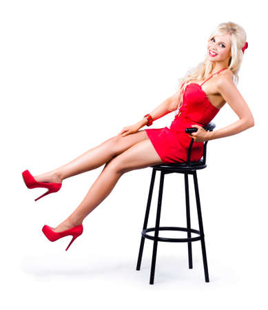 Glamorous blond pinup girl in red dress and matching shoes kicking back a pose on a bar stool, isolated on white background Stock Photo