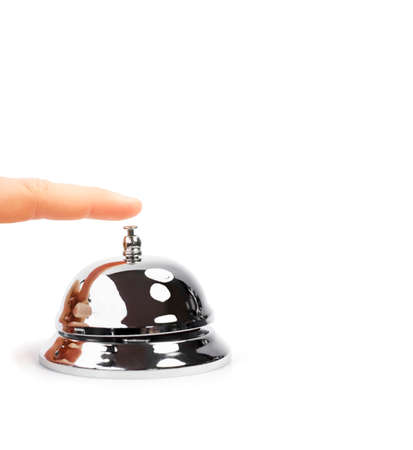 summon: Finger Pushing Service Bell. A finger pushing a shiny domed desktop service bell in a service, hospitality and help concept.
