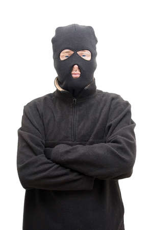 conman: A Smug Looking Masked Assailant Stands With His Arms Crossed Front On In A Studio Portrait